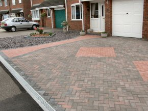 Herringbone block paving with coloured pavers and edging to define pathway and pattern area in Taunton. Aco channel leads to a soakaway. A raised flower bed is formed, and a slate area is formed to the right of the driveway.
