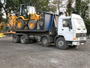 Roll on roll off lorry carrying JCB